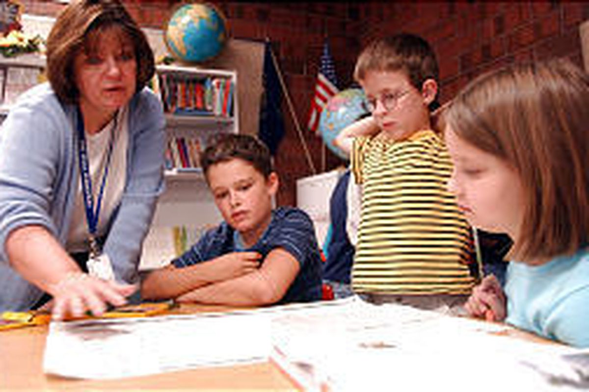 Fourth-grade students Logan Rainey, Alex Penfold and Emily Pearson work on a project with their teacher, Joan Johnson at Fox Hills Elementary School.
