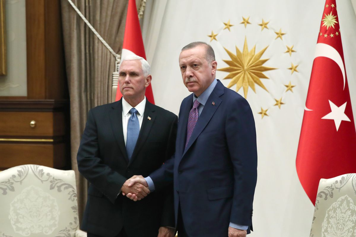 Vice President Mike Pence shakes hands with Turkish President Recep Yayyip Erdoğan in front of Turkish flags.