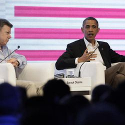 Colombia's President Juan Manuel Santos, left, sits next to President Barack Obama who speaks to an audience gathered at the CEO Summit of the Americas, in Cartagena, Colombia, Saturday April 14, 2012. Regional business leaders are meeting parallel to the sixth Summit of the Americas which brings together presidents and prime ministers from Canada, the Caribbean, Latin America and the U.S.