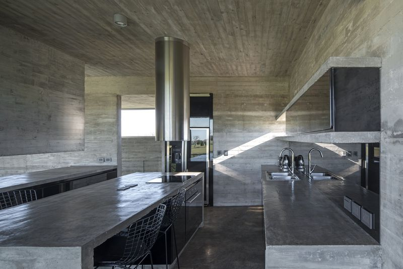 Dimly lit concrete kitchen.