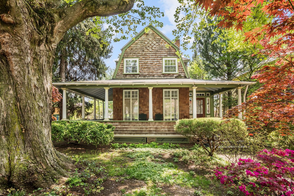 A shingle-style Victorian home with a large wrap-around porch.