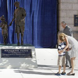 Cooper Stone, 7, hugs his mother, Jenny Stone, as Texas Rangers owner Nolan Ryan, rear, watches during the dedication for a statue of Shannon Stone, the fan who died after falling out of the stands trying to catch a ball in 2011, Thursday, April 5, 2012, in Arlington, Texas. The statue depicts Shannon with his son, Cooper, who he was with at the baseball game.