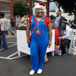 """No, she's not a Mario x Hello Kitty mashup. Attendee Carolyn Molina dressed up as the <a href=""""http://hellokittyworld.tripod.com/history/"""">OG Hello Kitty</a>, complete with blue overalls."""
