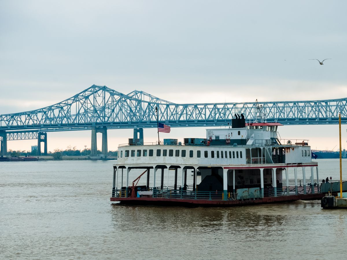 A ferry sits in front of a bridge on the Mississippi River
