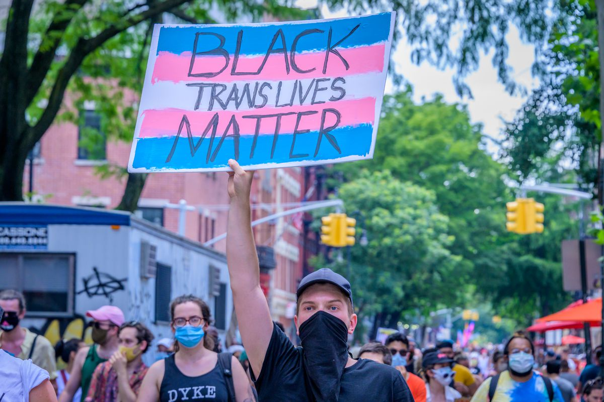 A protester holding a Black Trans Lives Matter sign.
