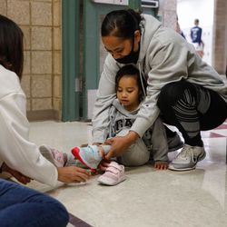 Vika Palei helps her daughter Akesa Palei, 2, with her new shoes donated by the Larry H. & Gail Miller Family Foundation on Thursday, Sept. 16, 2021, at Mountain View Elementary School in Salt Lake City. The foundation donated 1,000 pairs of Asics running shoes to underserved girls participating in the Girls on the Run Utah character development program.