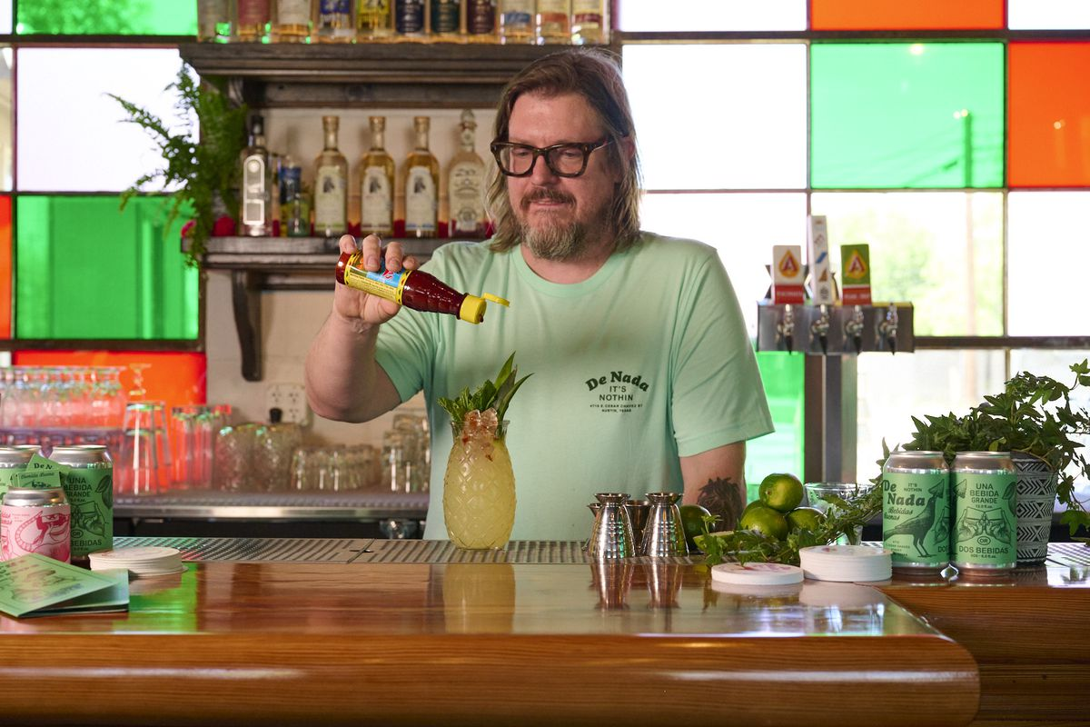 A bartender topping a drink in front of a colorful window