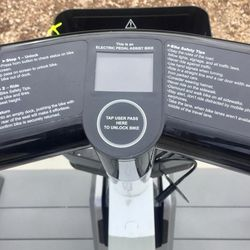 Instructions for use are attached to the handlebars of a Summit Bike Share electric bike.