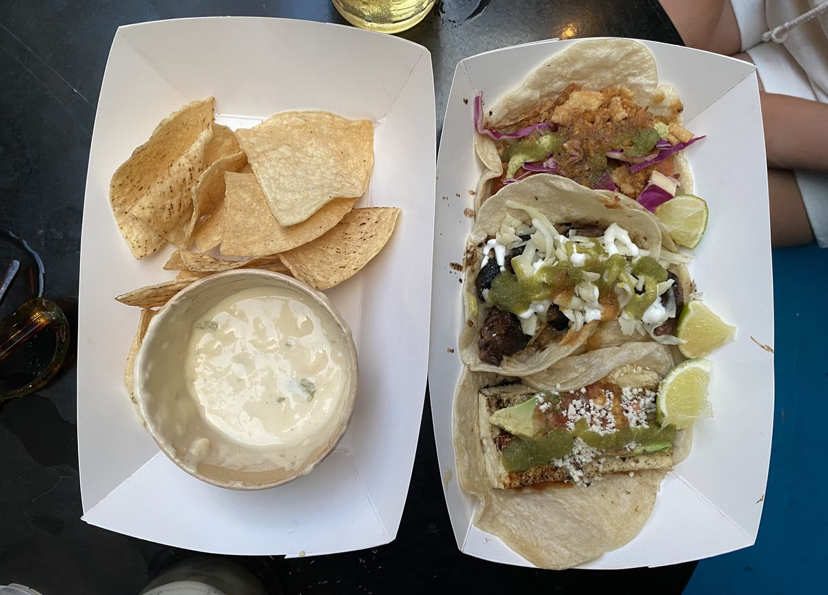 An overhead photograph of two paper takeout containers, one filled with chips and queso and another lined with three tacos