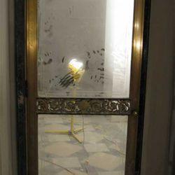 A reclaimed bronze door with intricate trim