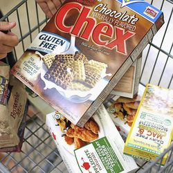 In this Sept. 20, 2012 photo, Katie Myers, 25, puts gluten-free chocolate Chex into her cart while shopping at a grocery store in Sycamore, Ill. Myers has been eating gluten-free for about six years.