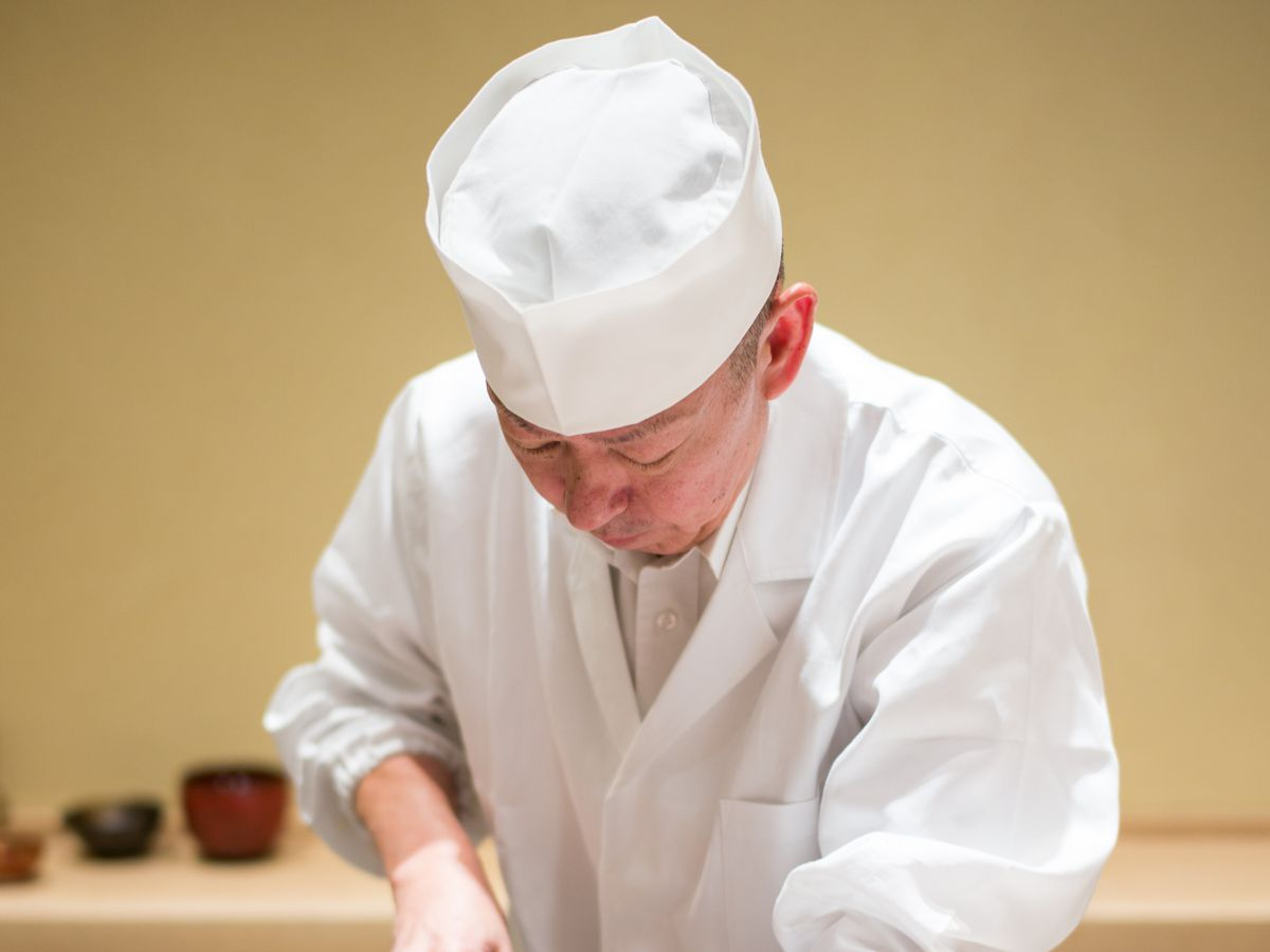 Eiji Ichimura wearing chef's whites and a white hat behind a sushi counter.