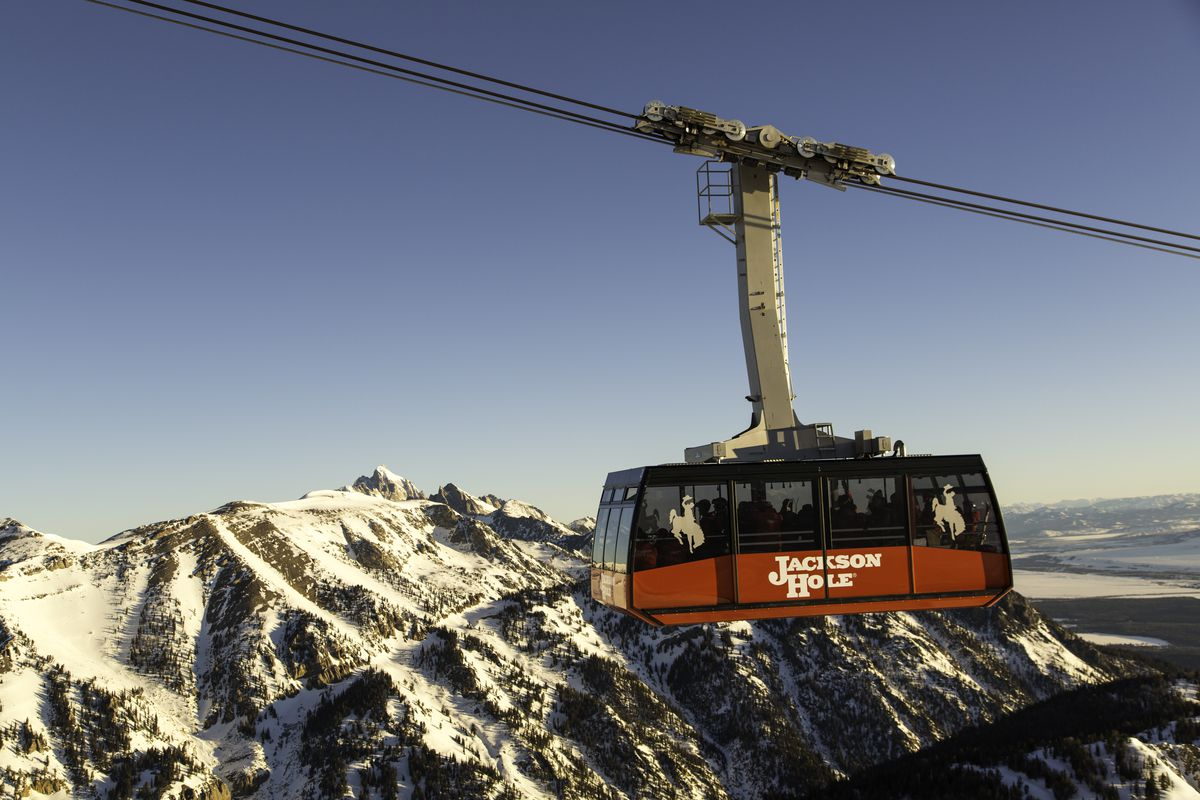 A view of the Jackson Hole Mountain Resort tram. The tram is red and is traveling on a cable above mountains that are covered in snow.