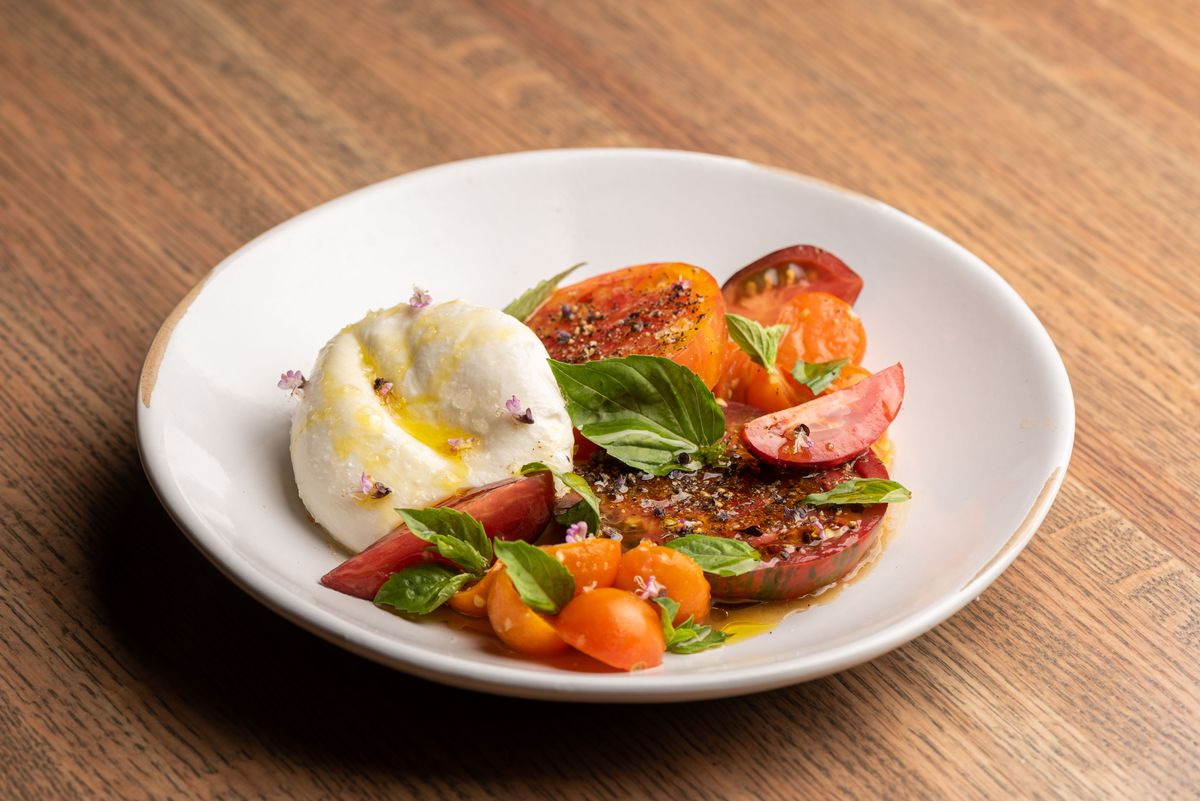 A white circular plate on a wooden table with burrata cheese and tomatoes.