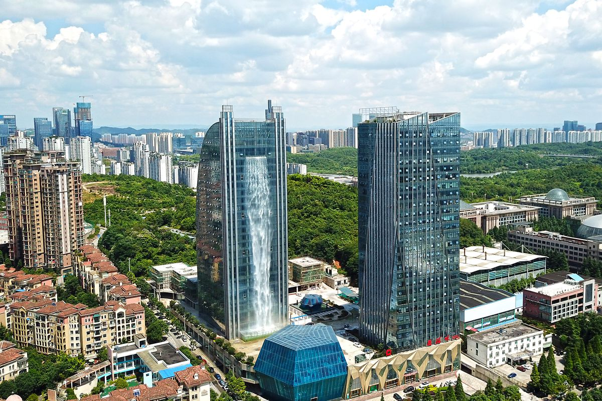 GUIYANG, CHINA - JULY 20: An artificial waterfall comes down from a 121-meter-tall office building on July 20, 2018 in Guiyang, Guizhou Province of China. (Photo by VCG)