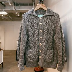 """<b>Strathtay Hand Knits</b> cardigan, <a href=""""http://store.inventorymagazine.com/collections/knitwear/products/cable-knit-lumber-cardigan-bracken"""">$400</a>"""