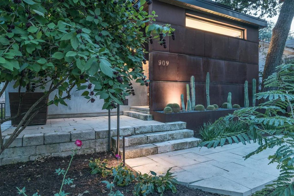 Twilight shot of front of contemporary wood and stucco home with corten steel planters