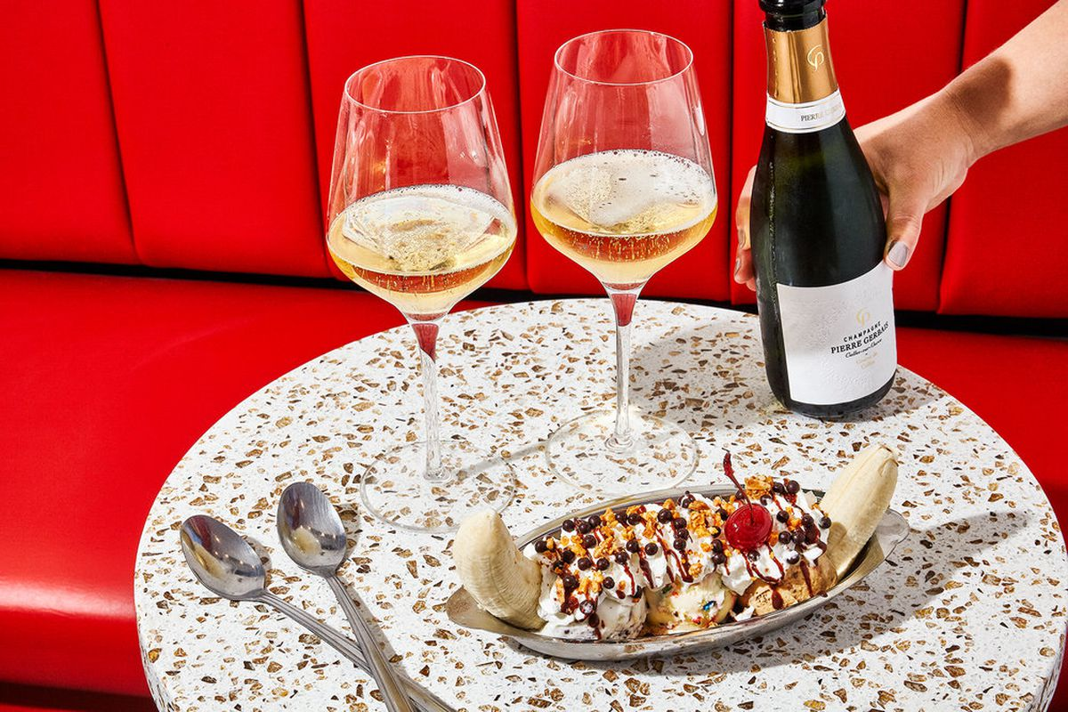 A banana split sits on a speckled table alongside two glasses of champagne and two spoons, with an arm reaching to place a bottle of champagne on the table
