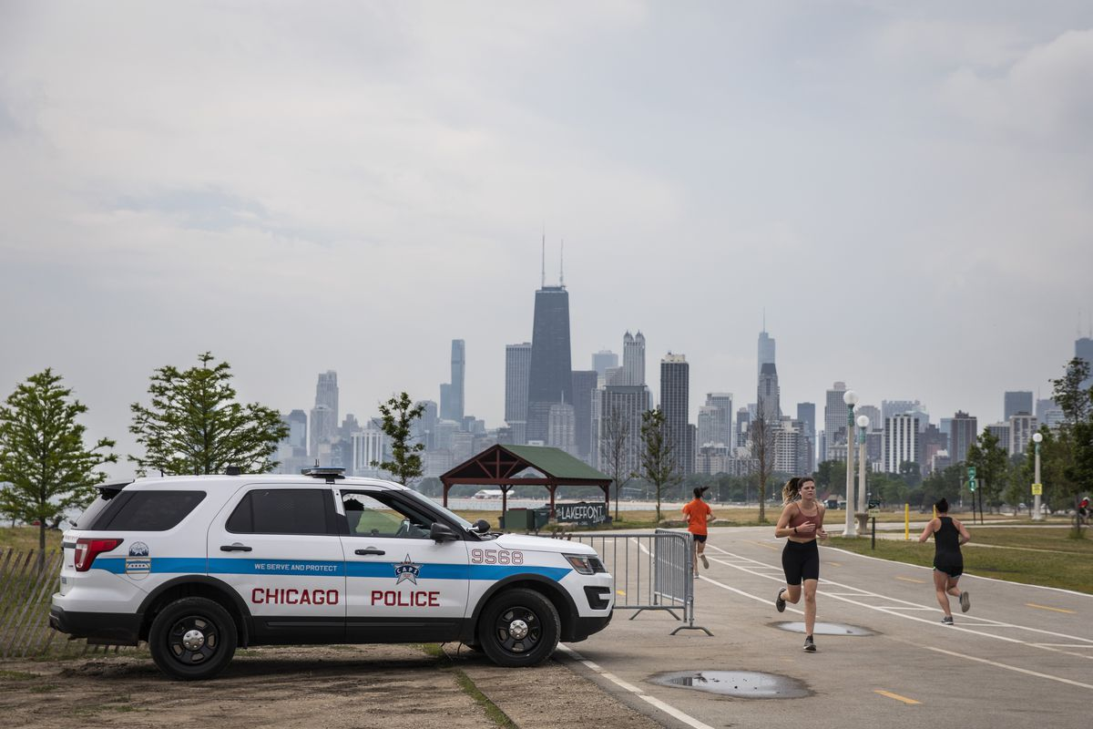 A Chicago Police officer keeps watch as people exercise on the Lakefront Trail near Fullerton Avenue on the North Side on Monday, the first day the park reopened to the public after being closed amid the coronavirus pandemic,