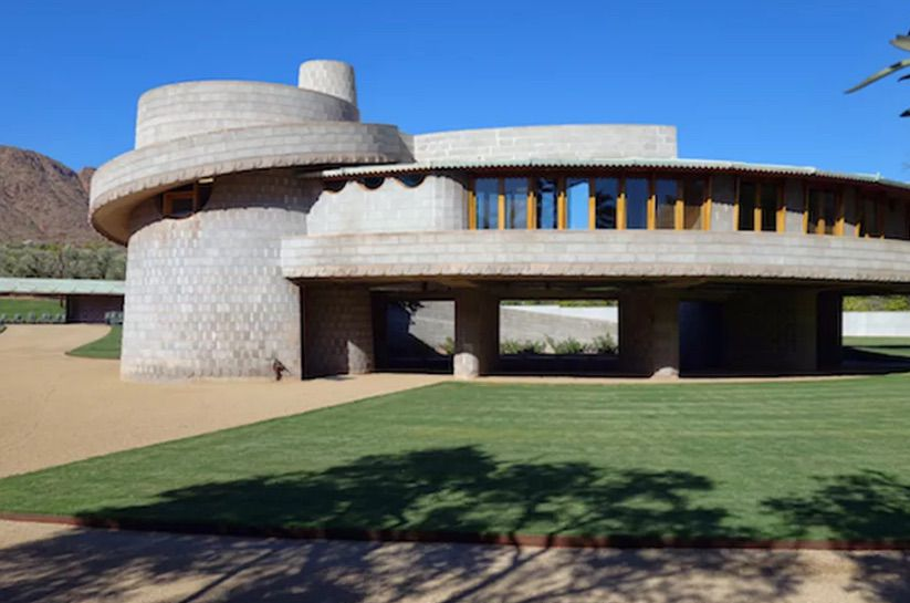 The David and Gladys Wright house by Frank Lloyd Wright. The house is grey brick with a curved shape and a circular structure on the side.
