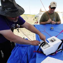 Weber State student Jeff Page, left, and Utah State University professor Randy Martinez get ready to  launch an aerostat used to study ozone at Ogden Bay Waterfowl Management Area near the Great Salt Lake Wednesday, June 17, 2015. The Utah Department of Environmental Quality's air quality scientists and researchers from Utah universities are deploying sensors this summer to detect smog-forming ozone.
