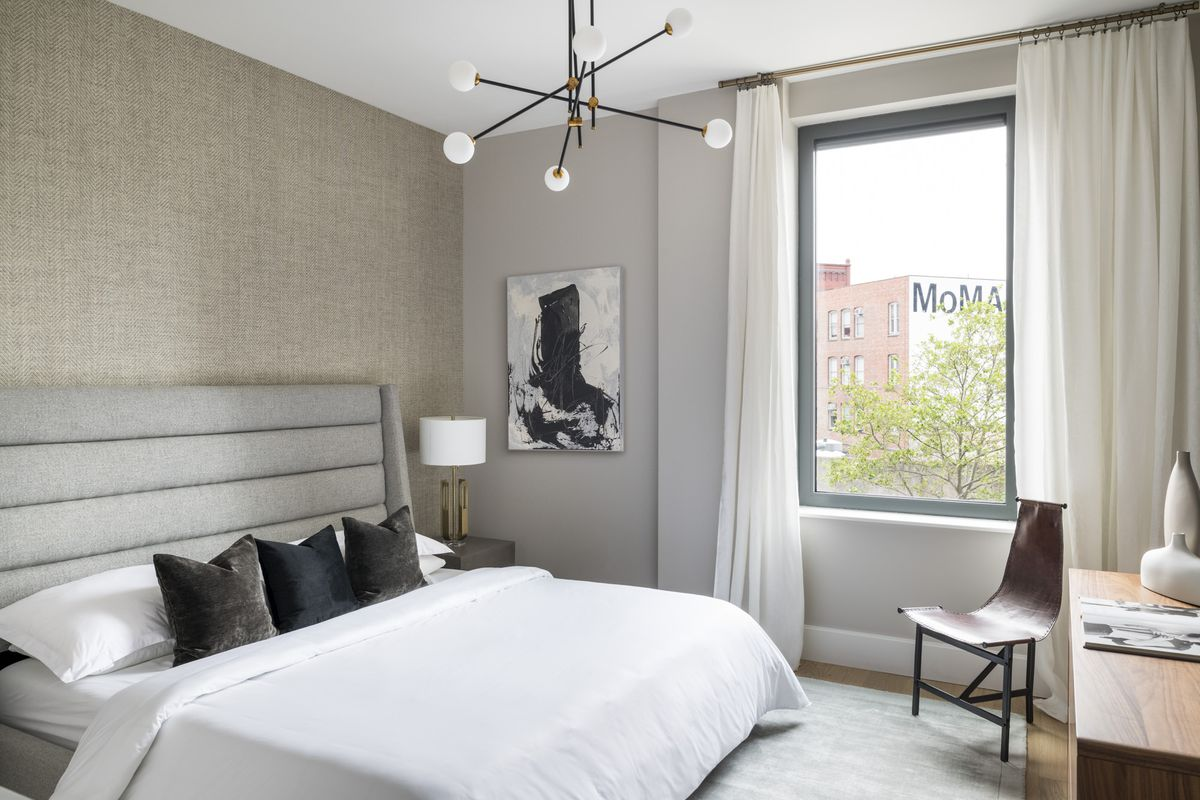 A bedroom with a large bed, a large window, a grey rug, and beige curtains.