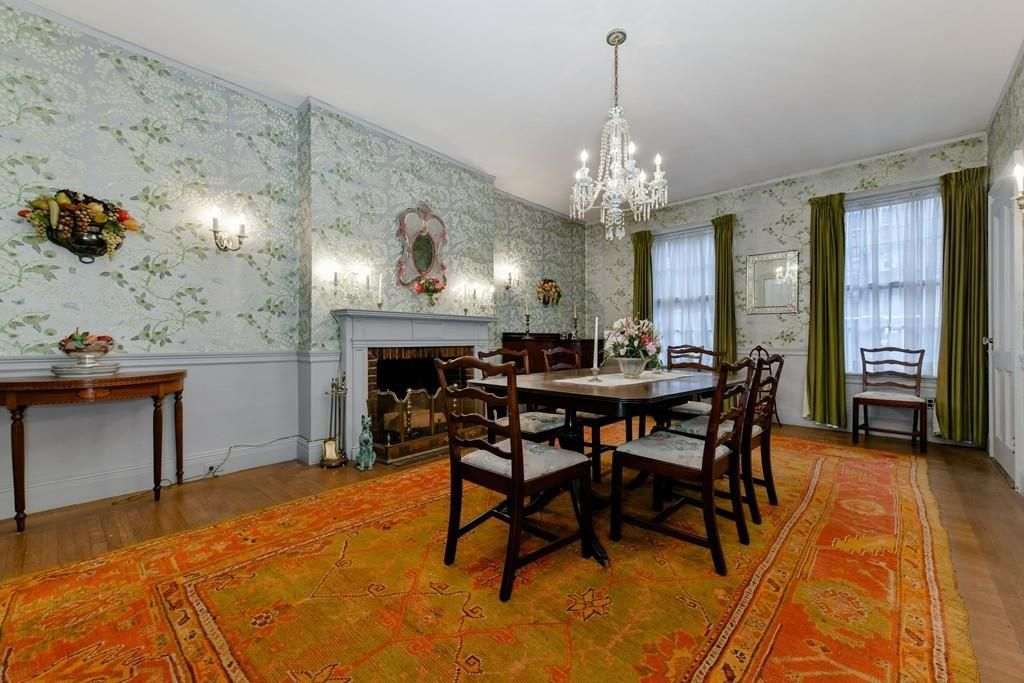 A dining room with a table and chairs as well as a fireplace.