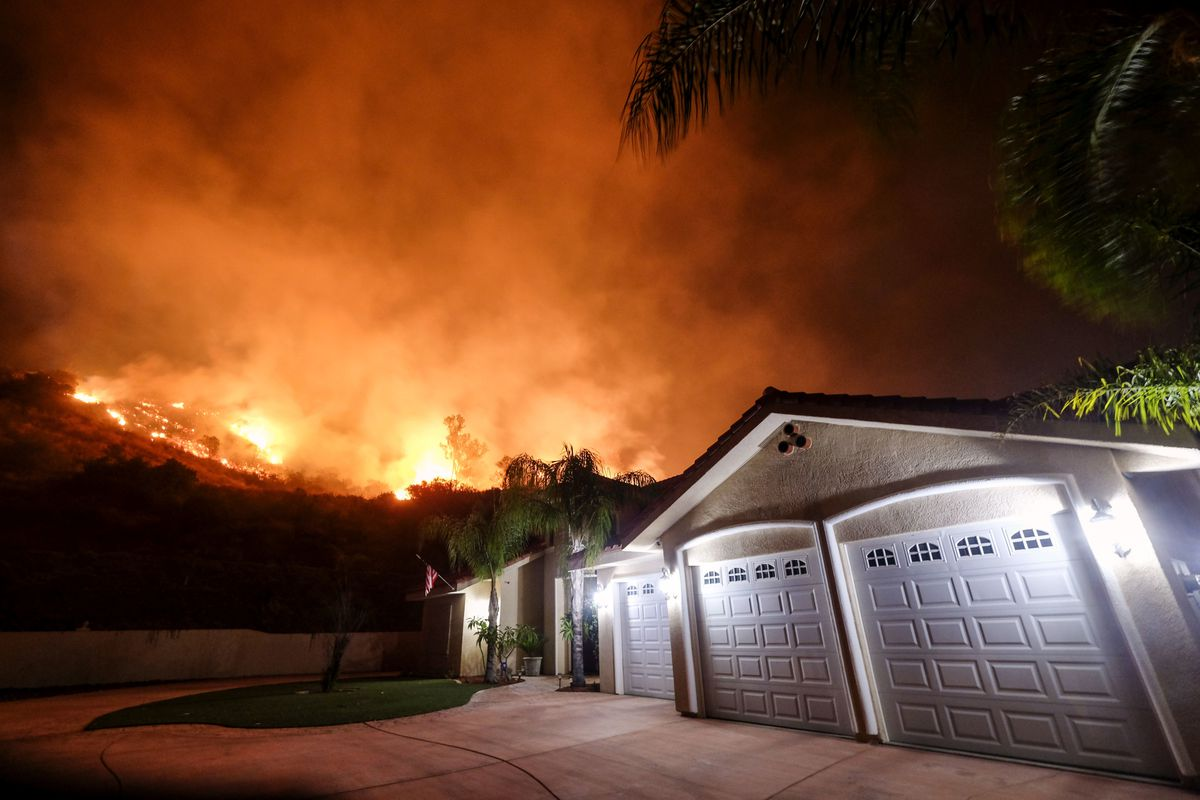 In this Aug. 9, 2018, file photo a wildfire burns near homes in the Cleveland National Forest in Lake Elsinore, Calif.