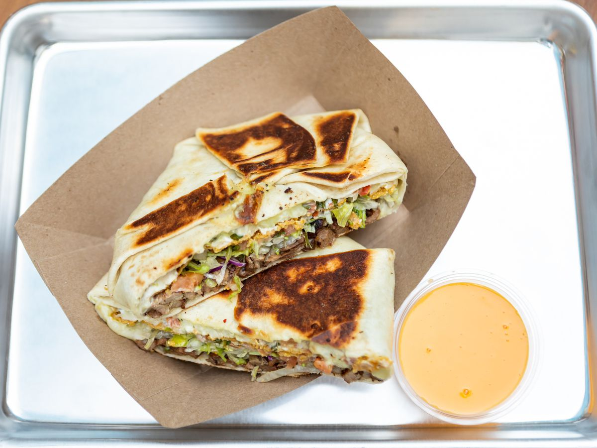 sisig crunchwrap with cheese dip on an aluminum tray
