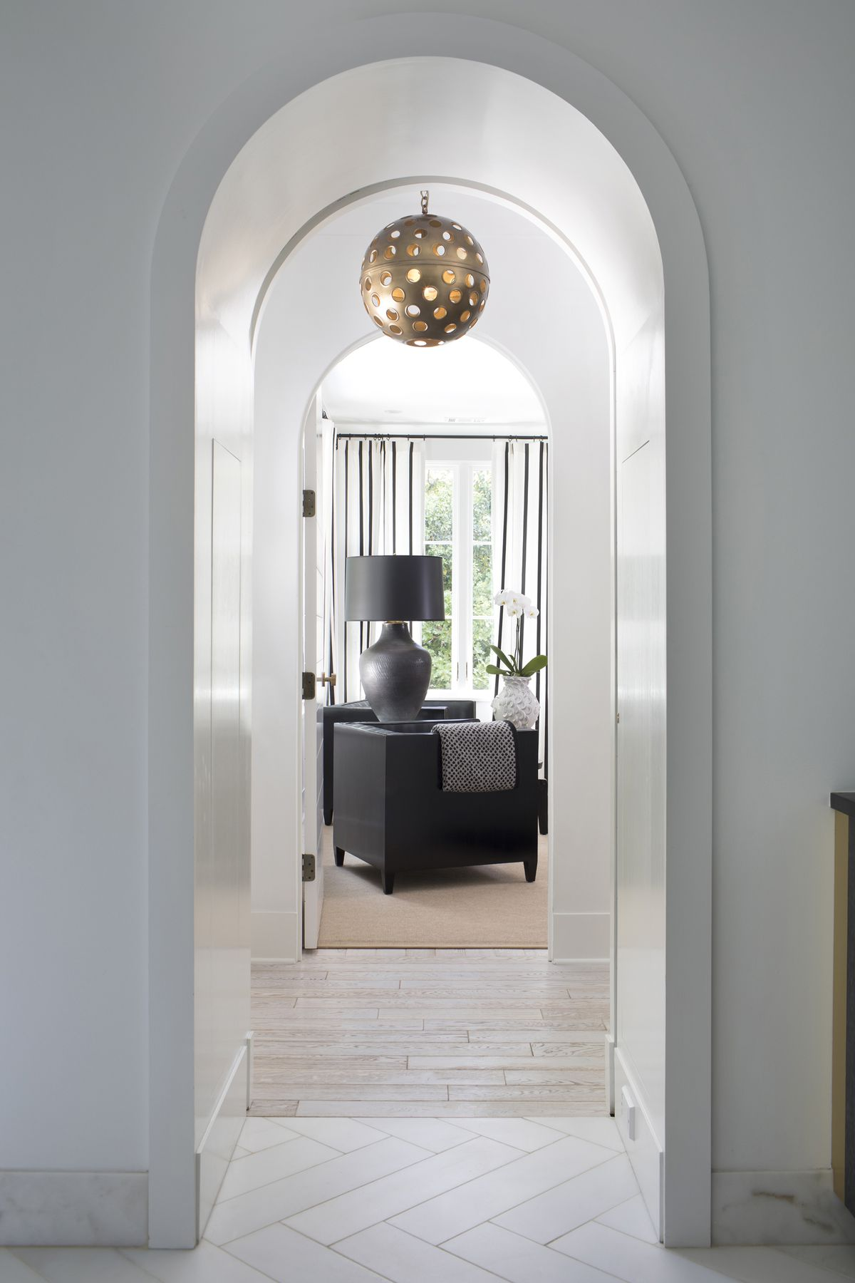 A series of arched doorways frame a large, circular light fixture pierced by circles.