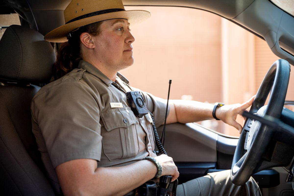 National Park Service ranger Melissa Hulls, the visitor and resource protection supervisor for Arches National Park, poses for a photo in her truck inside the park near Moab on Sunday, Sept. 19, 2021.