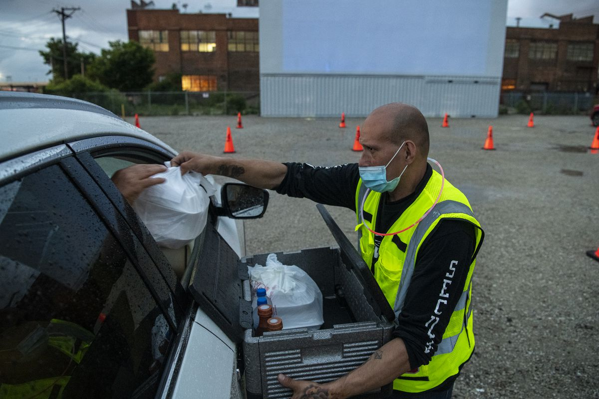 Manny Rodriguez, head of security at ChiTown Futbol, hands food to a moviegoer at ChiTown Movies on Tuesday, the facility's first night of drive-in movies in its parking lot.