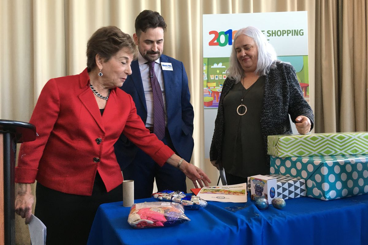 """U.S. Rep. Jan Schakowsky (D-Evanston), left, and Abe Scarr, Illinois director of the U.S. PIRG Education Fund, and Nancy Cowles, executive director of Kids in Danger, are standing at a table looking at children's """"slime"""" and other toys."""