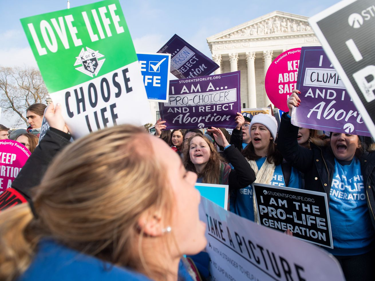 """Anti-abortion activists, including one holding a sign reading """"Love life, choose life,"""" as well as abortion-rights activists, demonstrate at the March for Life outside the US Supreme Court in Washington, DC, on January 18, 2019."""
