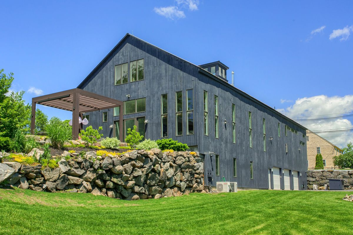 Large farmhouse with dark timber cladding and narrow windows on grassy lot.