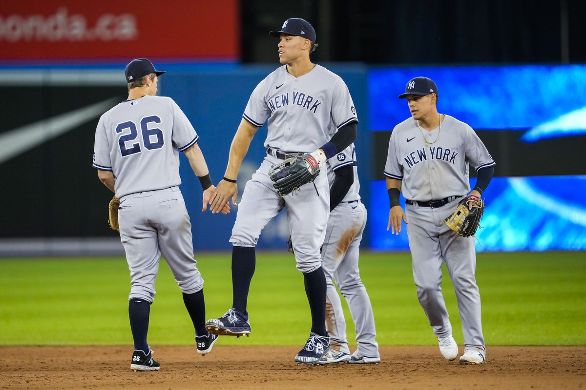Aaron Judge #99, Gio Urshela #29, and DJ LeMahieu #26 of the New York Yankees celebrate defeating the Toronto Blue Jays following their MLB game at the Rogers Centre on September 28, 2021 in Toronto, Ontario, Canada.