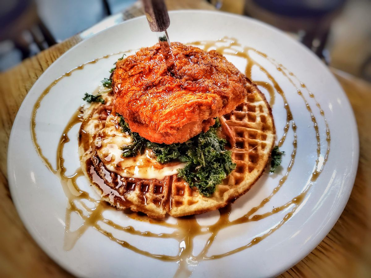 Buffalo style hot chicken sits on top of kale and a waffle, with syrup drizzled all over