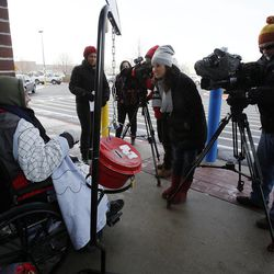 Doug Holladay, a former Salvation Army worker who is fighting terminal lung cancer, is interviewed as he rings a bell for donations a final time in Riverdale, Thursday, Dec. 5, 2013.