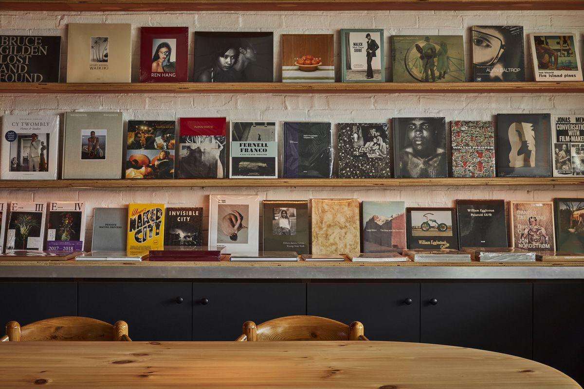 A bookshelf on white brick walls with art books and photo books sitting over and near a light wood table.