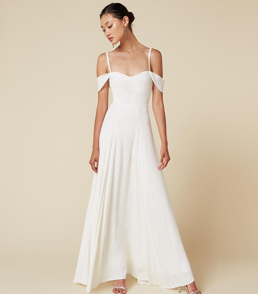 A model wearing an off the shoulder ivory Reformation wedding dress