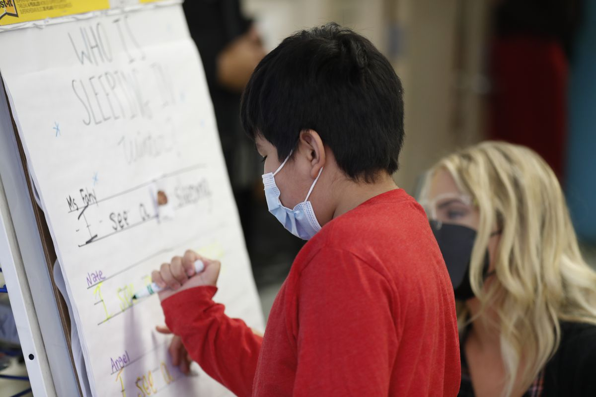 A student draws with a marker on a big sheet of paper on the first day of Chicago's second school reopening.