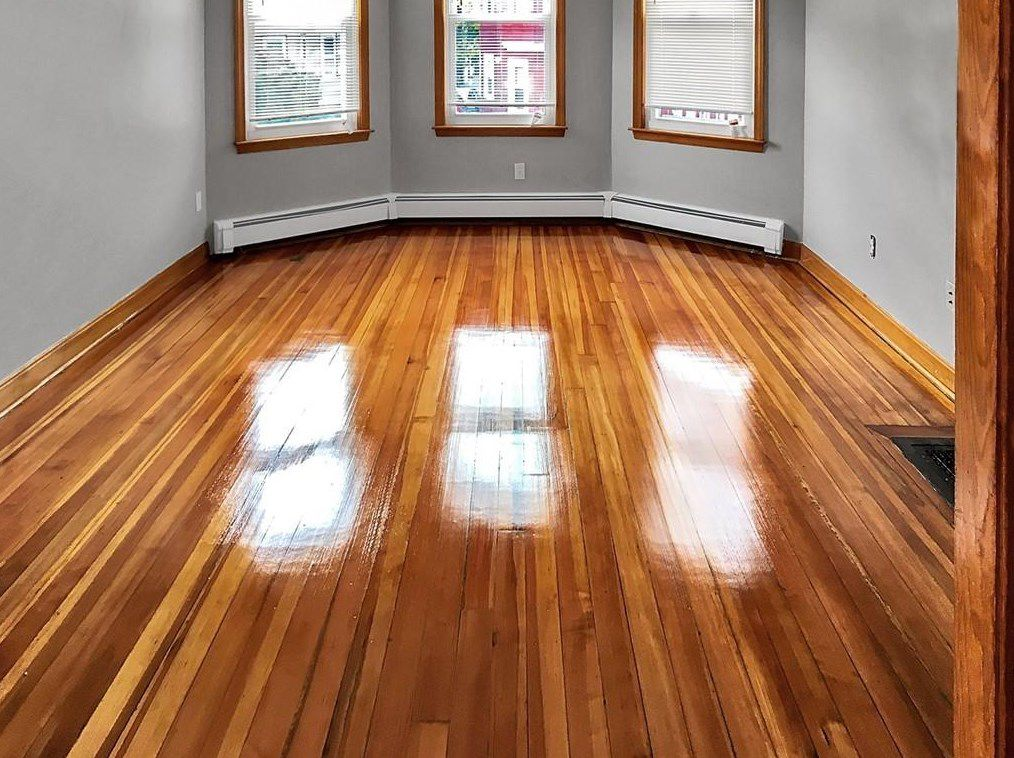 An empty living room with a bay window and a very shiny hardwood floor.