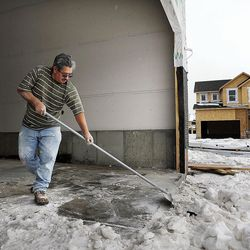 Before doing sheetrock work, Luis Martinez clears snow from the garage floor of a home being built in Farmington on Thursday, Feb. 4, 2016,