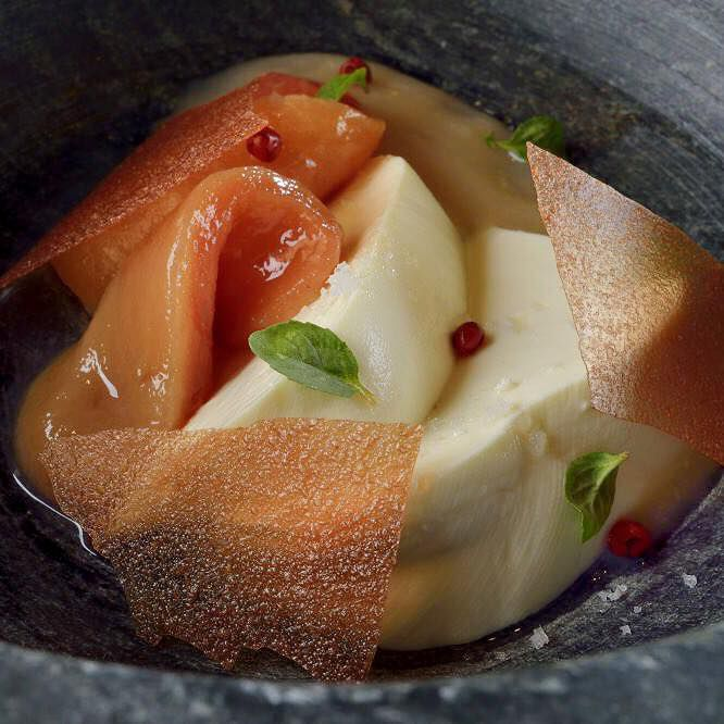 A close-up on a bowl of cheese and guava, both in various textures and preparations, in a broth with a few herbs sprinkled on top