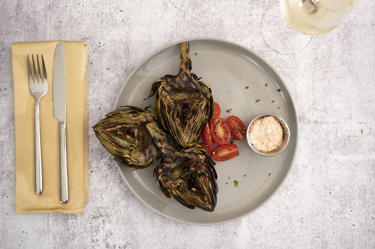 an overheat view of a plate with three grilled artichoke halves, some cherry tomatos and dipping sauce, next to a napkin and cutlery