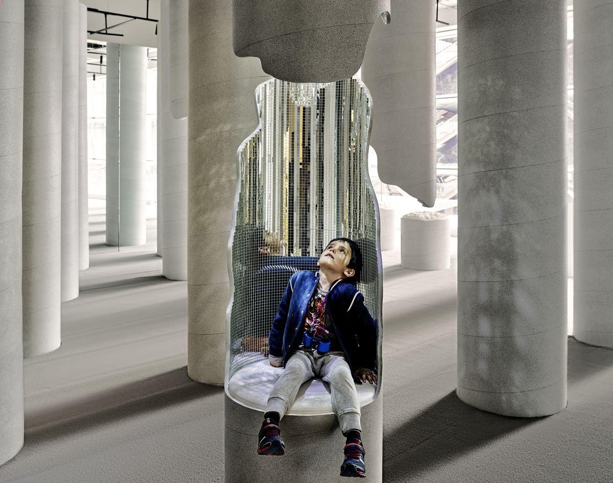 Child sitting in column cutout