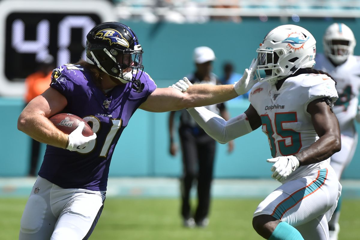 Hayden Hurst of the Baltimore Ravens stiff arms Walt Aikens of the Miami Dolphins in the third quarter of the game at Hard Rock Stadium on September 8, 2019 in Miami, Florida.