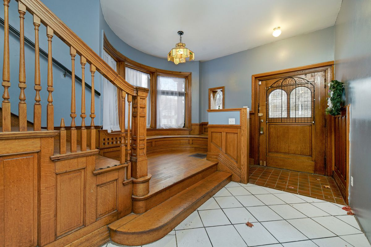 Just inside the home, there's brown tiles in the vestibule next to the large front door. White tiles line the foyer next to the wide wood staircase.