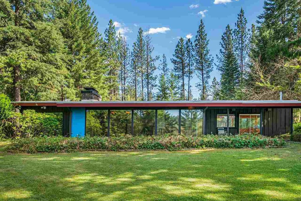 A low-profile home with overhanging roof and glass expanses on grassy site.