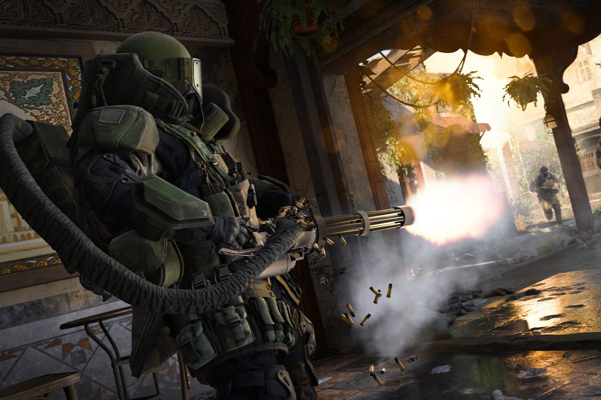 A player wearing heavy Juggernaut armor aims a minigun at another player in a bombed-out cafe in a screenshot from Call of Duty: Modern Warfare (2019)